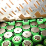 green-jacketed battery cells arranged in a hexagonal grid with a copper electrical interconnect above